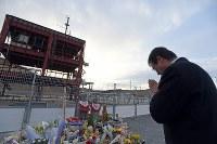 防災対策庁舎前で手を合わせる井上誠さん。町職員だった長男の翼(たすく)さんが津波で流されて亡くなった。庁舎の解体を望む一方、「翼の最期の場所だから」と月命日には必ず足を運んでいる=宮城県南三陸町で2016年3月11日午後4時54分、喜屋武真之介撮影