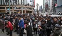 東日本大震災発生時刻に合わせて商業施設の鐘が打ち鳴らされ、路上で黙とうする人たち=東京・銀座で2016年3月11日午後2時46分、丸山博撮影