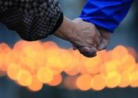 東日本大震災から5年を迎え、愛島東部仮設住宅に並べられた竹灯籠を囲んで手をつなぐ参加者=宮城県名取市で2016年3月11日午後5時34分、佐々木順一撮影