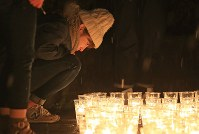 雪が降る中、キャンドルを見つめる人たち=宮城県名取市で2016年3月11日午後6時52分、佐々木順一撮影