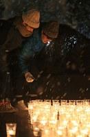 雪が降る中、キャンドルに火を灯す人たち=宮城県名取市で2016年3月11日午後6時51分、佐々木順一撮影