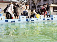 Women draw water from a swimming pool at Fukushima Daisan Elementary School in the city of Fukushima to flush lavatories on March 13, 2011.(Copyright (c) Fukushima-Minpo Co., Ltd.)