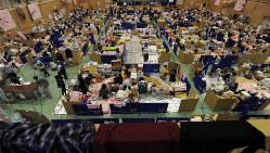 東日本大震災で避難所になった陸前高田市の中学校体育館。被災した人たちは食料や日用品と一緒に情報を求めていた=2011年5月
