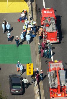 多重事故が起きた八本松トンネル付近に集まる消防隊員ら=広島県東広島市で2016年3月17日午前10時48分、本社ヘリから三浦博之撮影