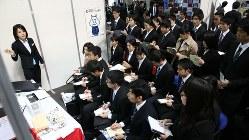合同企業説明会で担当者から説明を聞く学生ら=インテックス大阪で2016年3月1日