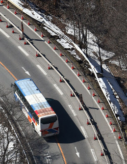 同型車両(左)を走らせ事故現場付近で行われた実況見分。右側にはバスが突っ込んで壊れたガードレールが残る=長野県軽井沢町で2016年3月17日午後2時38分、本社ヘリから後藤由耶撮影