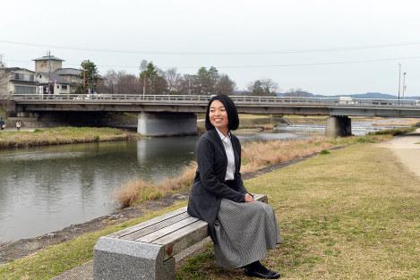 賀茂川沿いのベンチに座り、景色を見つめる彬子さま。奥は葵橋=京都市左京区で、小松雄介撮影