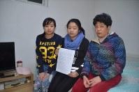 22歳になっても戸籍に登録されず、母親(右)や姉(左)と協力しながら生きてきた李雪さん=北京市で、工藤哲撮影