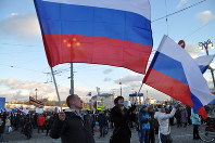 ロシアのプーチン政権がクリミア半島を一方的に編入して2年となった18日、モスクワで開かれた記念集会。政権支持者らが国旗を振ったが、参加した市民は限定的だった=モスクワ中心部で2016年3月18日、真野森作撮影