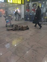In this photo provided by Georgian Public Broadcaster and photographed by Ketevan Kardava a man is wounded in Brussels Airport in Brussels, Belgium, after explosions were heard Tuesday, March 22, 2016. (Ketevan Kardava/ Georgian Public Broadcaster via AP)