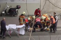 In this image made from video, emergency rescue workers stretcher an unidentified person at the site of an explosion at a metro station in Brussels, Belgium, March 22, 2016. (APTN via AP)