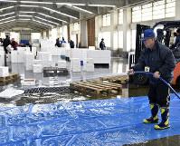 競りが終わり、ズワイガニが並べられていたブルーシートを洗う山岡さん=鳥取県岩美町で、高嶋将之撮影