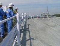 防波壁の盛り土の上で説明を聞く県の担当者ら=御前崎市の中部電力浜岡原発で