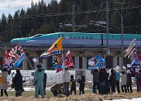 People wave fishing boat flags as the first train from Tokyo on the newly-opened Hokkaido Shinkansen Line, the