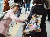石綿健康被害救済法施行10年となり、チラシを配布する参加者=JR尼崎駅前で、釣田祐喜撮影