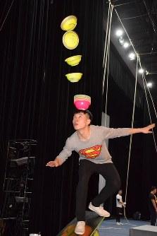 公演前に練習に励む団員。不安定な板の上で、わんを空中に飛ばし、頭の上に重ねる技だ=上海で2016年3月17日、林哲平撮影