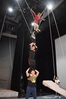 公演前の練習に励む上海雑伎団のメンバー。はねあげられた板によって空中に飛んだ女性が3人のメンバーの上に飛び乗る技だ=上海で2016年3月17日、林哲平撮影