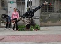 練習場のある住宅街の路上で雑伎に取り組む民間雑伎団「上海の夢」の団員たち=上海市で2016年3月21日、林哲平撮影