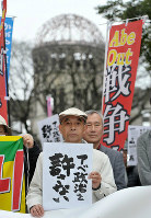 Hibakusha (atomic bomb survivors) are seen in front of the Atomic Bomb Dome in the city of Hiroshima's Naka Ward protesting against the enforcement of security-related legislation on March 29, 2016. (Mainichi)