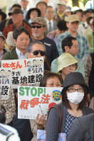 Participants are seen calling for the abolishment of security-related legislation in a demonstration held in front of the Okinawa Prefectural Government offices in the city of Naha on March 29, 2016. (Mainichi)