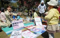 Women are seen drinking tea at a park in front of the National Diet Building in Tokyo's Nagatacho district while protesting the enforcement of security-related legislation on March 29, 2016. (Mainichi)