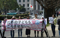 Women are seen in Tokyo's Nagatacho district holding an unfurled banner protesting security-related legislation following its enforcement on March 29, 2016. The National Diet is seen in the background. (Mainichi)