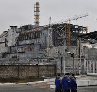 1986年4月26日に爆発事故が起きたチェルノブイリ原発4号機。現在は「石棺」と呼ばれるコンクリート製シェルターで覆われているが、老朽化が目立つ。隣接地では金属製の新シェルターの工事が続いており、関係者が行き交う=チェルノブイリ(ウクライナ北部)で2016年2月10日、真野森作撮影