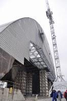 1986年4月26日に爆発事故が起きたチェルノブイリ原発4号機の隣接地で、金属製の巨大な新シェルターの工事が続く。「石棺」と呼ばれる老朽化した現在のコンクリート製シェルターの上から4号機を覆う計画だ=チェルノブイリ(ウクライナ北部)で2016年2月10日、真野森作撮影