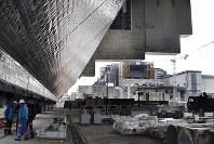 1986年4月26日に爆発事故が起きたチェルノブイリ原発4号機(奥)の隣接地で建設が続く、金属製の巨大シェルターの内部。現場の一部は除染され、工事関係者が作業着姿で行き交う=チェルノブイリ(ウクライナ北部)で2016年2月10日、真野森作撮影