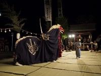 「刀舞」。夜空を背景に抜刀された太刀が怪しい光を放つ。本物の太刀で四隅を清める=松本成さん撮影