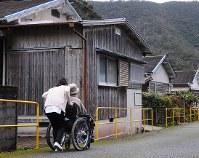 入所者の男性を散歩させる看護師。高齢化と入所者の減少で、和光園内には空き家も目立つ=石井尚撮影