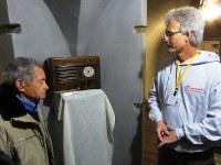 防空壕内に置かれたラジオからはムソリーニ辞任の臨時ニュース音声が流れる