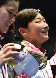 女子50メートル自由形決勝、優勝し、表彰式で笑顔を見せる池江璃花子(右)=東京辰巳国際水泳場で2016年4月10日、三浦博之撮影