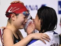 女子200メートル背泳ぎ決勝、優勝するも派遣標準記録を突破できず悔し涙を流す酒井夏海(左)。右は2位の川除結花=東京辰巳国際水泳場で2016年4月10日、三浦博之撮影