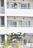 デモンストレーションで飛行する宅配用ドローン=千葉市美浜区で2016年4月11日午前10時40分、宮間俊樹撮影