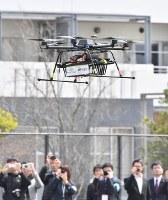 デモンストレーションで飛行する宅配用ドローン=千葉市美浜区で2016年4月11日午前10時41分、宮間俊樹撮影