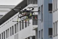 デモンストレーションで飛行する宅配用ドローン=千葉市美浜区で2016年4月11日午前10時45分、宮間俊樹撮影