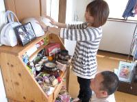 「毎朝、触れてから出勤するんです」。亡き娘2人のヘルメットに手を添える高橋千春さん(左)と清晃さん=宮城県登米市の自宅で