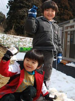 仮設住宅の前に降り積もった雪で遊ぶ及川律ちゃん(右)と詠ちゃん=岩手県陸前高田市で