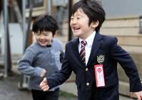 入学式当日。ネクタイ姿のまま、駆け回って遊ぶ及川律ちゃん(右)。その後ろを、詠ちゃんがずっと追いかけていた=岩手県陸前高田市で8日、小川昌宏撮影