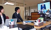 徳島県が設置した4カ所のサテライトオフィスと県庁を結んだテレビ会議システムで、飯泉嘉門知事から指示を受ける職員=徳島県神山町下分で、蒲原明佳撮影