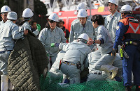 Workers from Sendai Yagiyama Zoological Park and others surround a chimpanzee that escaped from the zoo following its capture in Sendai's Taihaku Ward on April 14, 2016. (Mainichi)