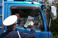 巻き込み死亡事故増加で、警察官の説明に耳を傾けるトラック運転手=大阪府警提供