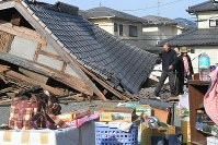 A family picks up the pieces after the collapse of their home due to the Kumamoto earthquake, in Mashiki, Kumamoto Prefecture, on April 15, 2016. (Mainichi)