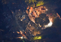 ライトに照らされながら、救出作業が続く地震で倒壊した建物=熊本県益城町で2016年4月14日午後11時37分、本社ヘリから矢頭智剛撮影