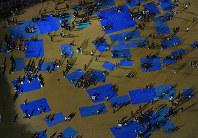 校庭にビニールシートを敷いて避難する人たち=熊本市北区で2016年4月14日午後11時49分、本社ヘリから矢頭智剛撮影