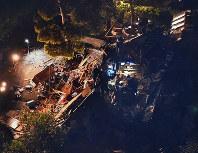 ライトに照らされながら、救出作業が続く地震で倒壊した建物=熊本県益城町で2016年4月14日午後11時36分、本社ヘリから矢頭智剛撮影