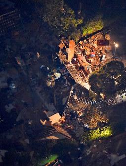 ライトに照らされながら、救出作業が続く地震で倒壊した建物=熊本県益城町で2016年4月14日午後11時38分、本社ヘリから矢頭智剛撮影