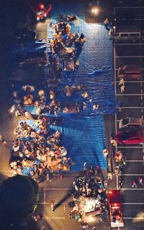地震の影響で駐車場に避難した人たち=熊本県益城町で2016年4月14日午後11時41分、本社ヘリから矢頭智剛撮影