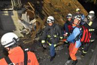 倒壊した建物の横を通って、救助した人を搬送する消防隊員ら=熊本県益城町で2016年4月15日午前0時38分、和田大典撮影